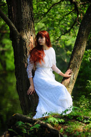 Young red-haired pretty woman on the summer park Stock Photo - 7539522