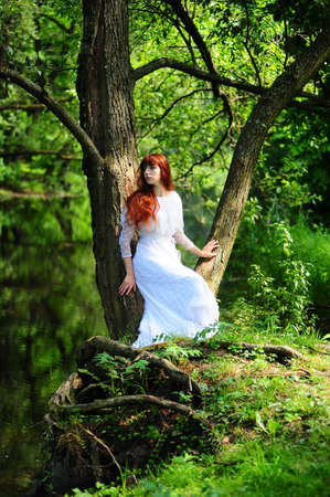 Young red-haired pretty woman on the summer park Stock Photo - 7539544