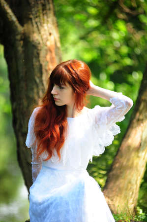 Young red-haired pretty woman on the summer park Stock Photo - 7539520