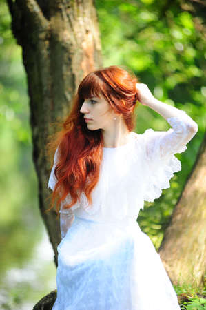 red haired woman: Young red-haired pretty woman on the summer park