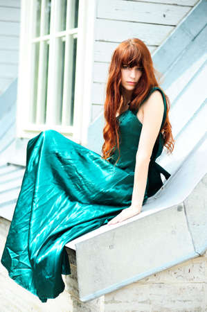 The girl in a green dress sitting on the brink of a roof photo