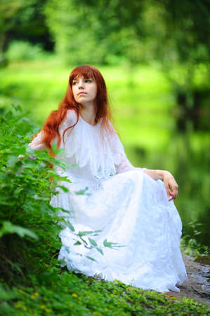 The girl in a white dress in park at the river photo