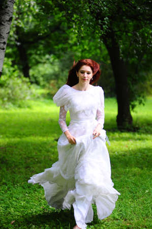 A beautiful caucasian  bride in her white wedding dress  running home and away from the wedding in the park outdoors photo