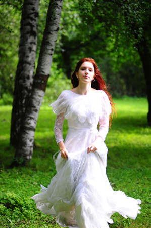 escaping: A beautiful caucasian  bride in her white wedding dress  running home and away from the wedding in the park outdoors