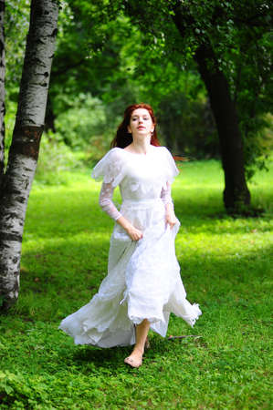 fleeing: A beautiful caucasian  bride in her white wedding dress  running home and away from the wedding in the park outdoors