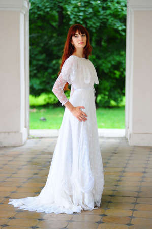 historical clothing: Portrait of a beautiful young victorian lady in white dress Stock Photo
