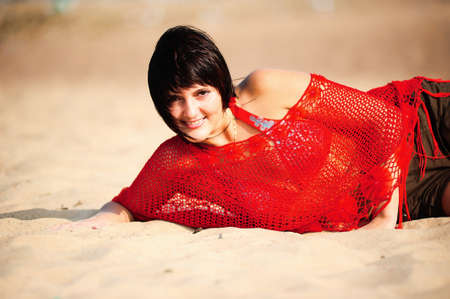 The beautiful young brunette in brightly red jacket lying on sand photo