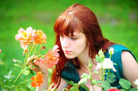 The red-haired girl near to roses photo