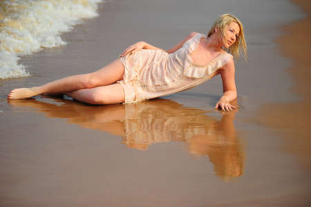 The girl in a dress lying on sand photo