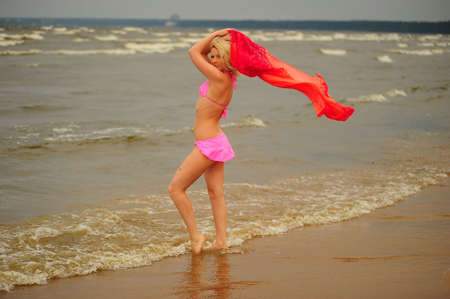 A beautiful young blond girl in a pink bikini and a chiffon scarf  photo