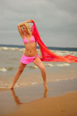 A beautiful young blond girl in a pink bikini and a chiffon scarf  photo