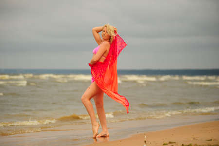 A beautiful young blond girl in a pink bikini and a chiffon scarf stands in the tradewinds on Kailua beach, Oahu, Hawaii photo