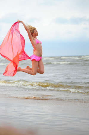 The girl jumping in a bathing suit against the sea Stock Photo - 7557615