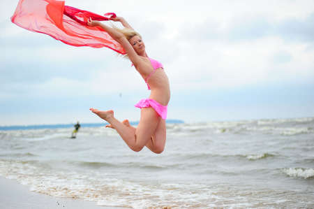 The girl jumping in a bathing suit against the sea Stock Photo - 7556175