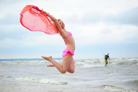 scarf beach: La ni�a saltando en un traje de ba�o contra el mar