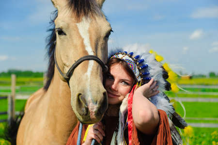 American Indian Girl petting her horse outside photo