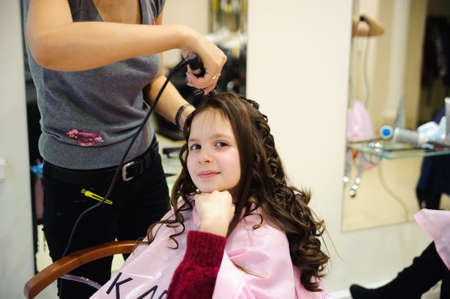 The little girl doing a hairdress in a hairdressing salon photo