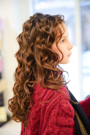 Portrait of the beautiful little girl of the brunette with a curly hair photo