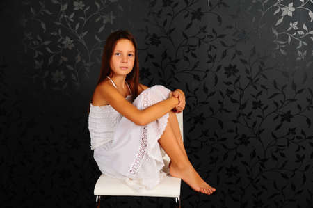 without clothes: The girl in white clothes sitting on a chair in studio