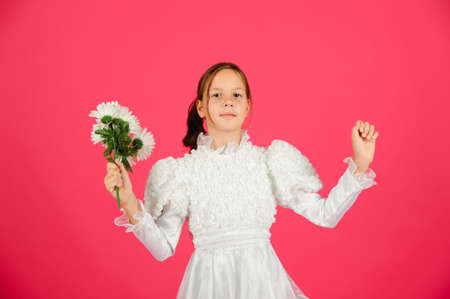 The little girl in a white dress on a pink background photo