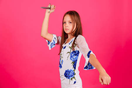The girl with a knife in a hand on a pink background in studio photo