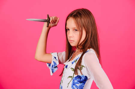 dagger: The girl with a knife in a hand on a pink background in studio