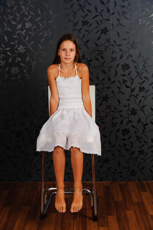 barefooted: The girl in white clothes sitting on a chair in studio