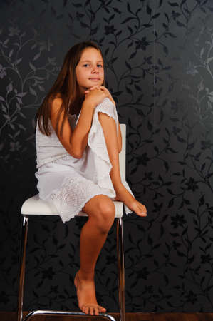 without people: The girl in white clothes sitting on a chair in studio