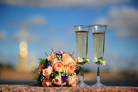 Bouquet of the bride and glasses with champagne