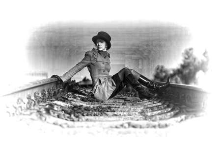 black and white railroad tracks:  Womnan is sitting on the rails