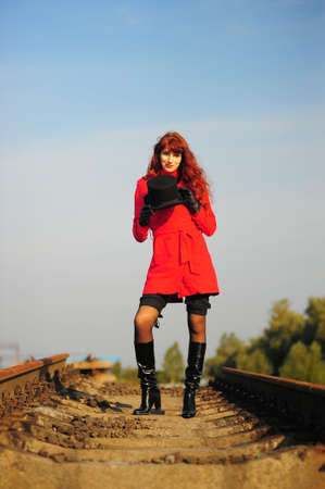 The young red-haired woman going on railroad tracks in brightly red jacket    photo