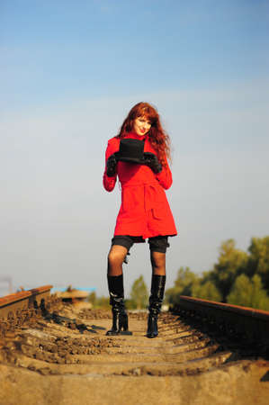 The young red-haired woman going on railroad tracks in brightly red jacket