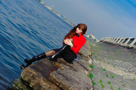 The girl sitting on quay at water photo