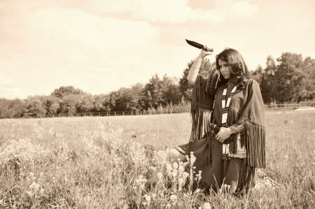 girl with knife: girl dressed as an Indian with a knife in his hand