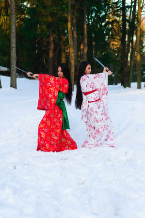Beautiful brunette girls in a japanese kimono with a katana Stock Photo - 8241047