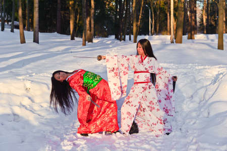 Two girls in a Japanese national dress, fighting with swords Stock Photo - 8241048