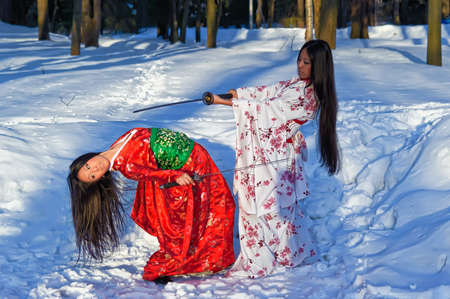Two girls in a Japanese national dress, fighting with swords photo