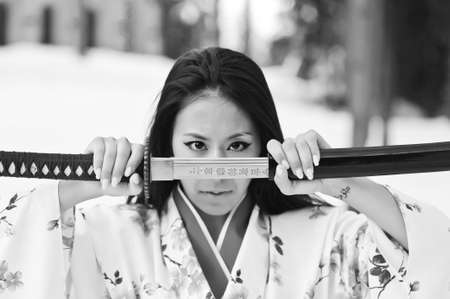 Young japanese woman with samurai sword fashion photo