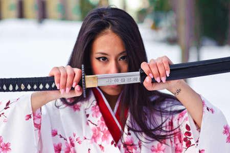 geisha kimono: Young japanese woman with samurai sword fashion Stock Photo