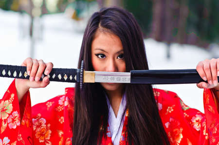 japanese kimono: Young japanese woman with samurai sword fashion Stock Photo