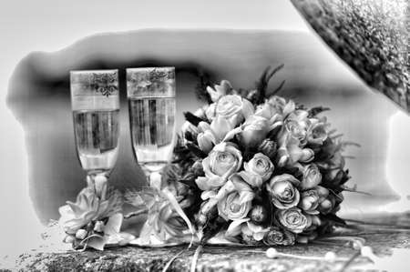 Photo of two glasses full of champagne with bridal bouquet of white roses near by. Photography done in retro style photo
