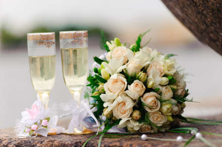 Photo of two glasses full of champagne with bridal bouquet of white roses near by.  photo
