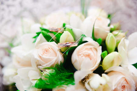 wedding rings and white roses photo