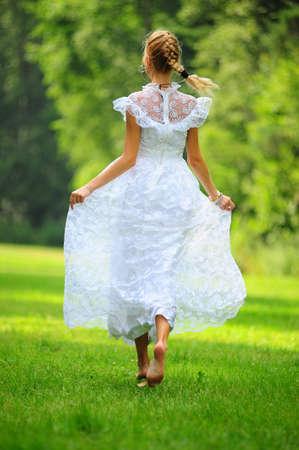 pieds nus femme: jeune fille en robe blanche dans le parc