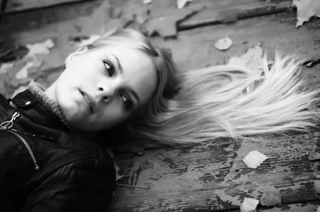 lying in leaves: Beautiful woman with blond hair and leaves on it lying on wooden floor  Stock Photo