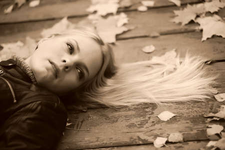 Beautiful woman with blond hair and leaves on it lying on wooden floor  photo