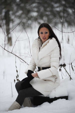 girl sitting on a stump in the winter forest Stock Photo - 8297925