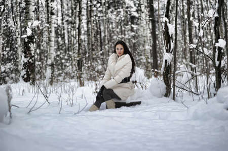 girl sitting on a stump in the winter forest Stock Photo - 8297946