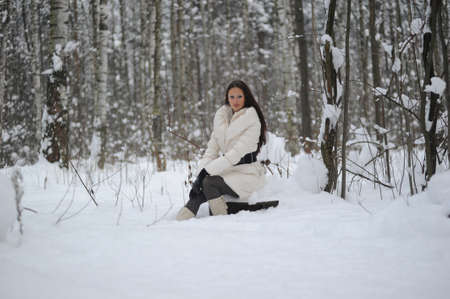 girl sitting on a stump in the winter forest Stock Photo - 8297939