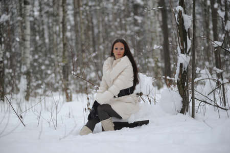 girl sitting on a stump in the winter forest photo